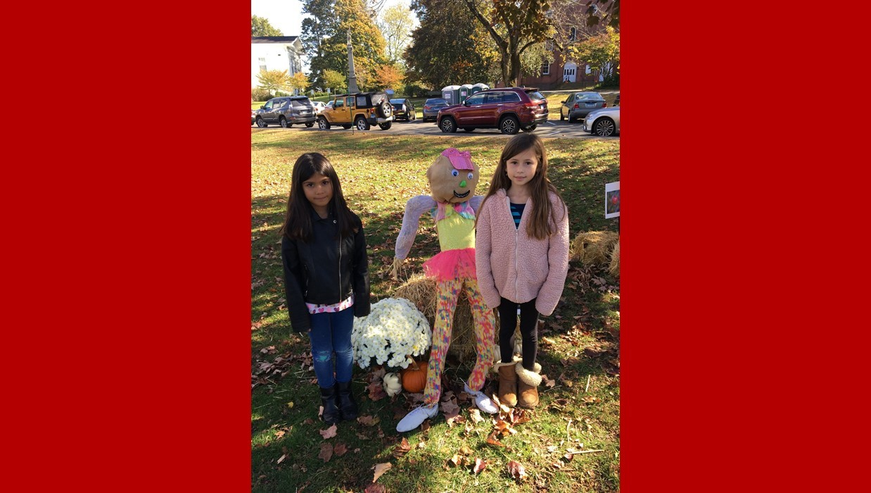 Two little girls standing next to a scarecrow