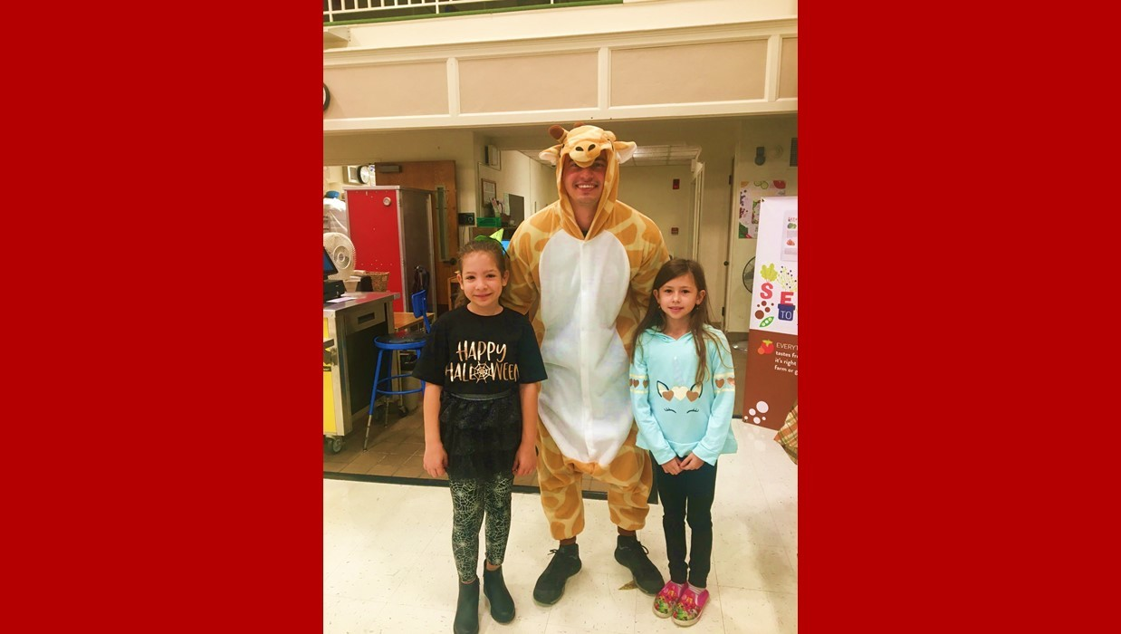 Male intern dressed as a giraffe for Halloween with 2 students