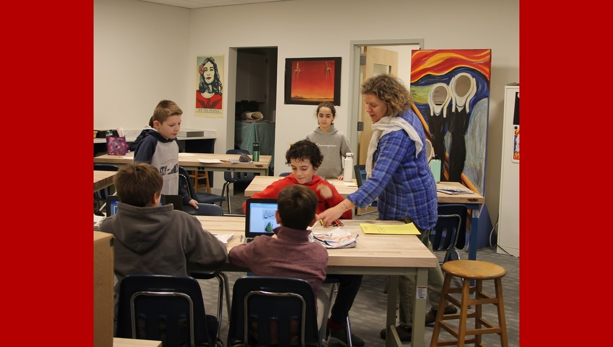 Students working with a teacher in art class
